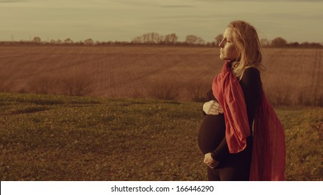 Lonely pregnant woman standing in a field worried about her future