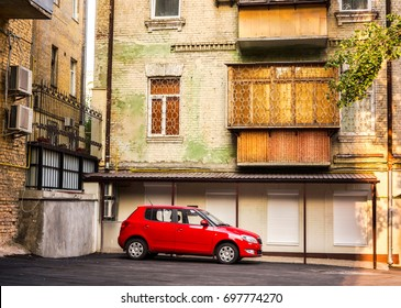 lonely red car is waiting for his master driver in the empty courtyard green multi-storey old house in a sunny day, empty car parked on a makeshift yard parking