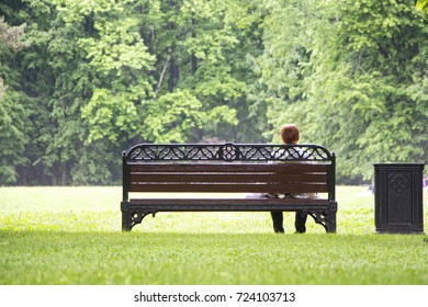 Lonely red-haired elderly woman sitting on a bench in a summer park