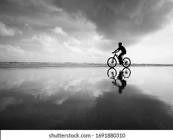 The lonely rider cycling on the beach with beautiful reflection in black and white. isolation and solitude