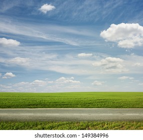 lonely road in the green field under blue sky