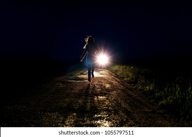 lonely running female silhouette on the night country road running away from pursuers by car in the headlights