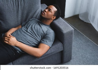 lonely sad african american man lying on sofa at home