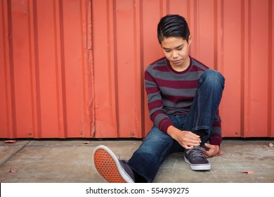 Lonely, sad Asian boy sitting back against a metal wall while gazing down.