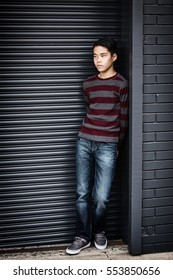 Lonely, sad Asian teenage boy standing in an outdoor corner.