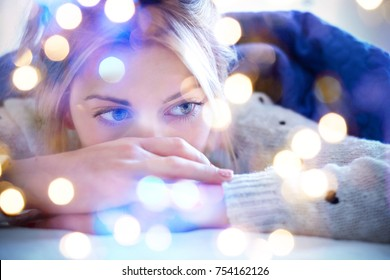 Lonely sad girl lying on bed in a bedroom , bokeh light balls illuminating the shot