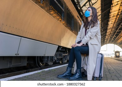Lonely sad girl in medical mask sits on suitcase waiting for train. Female traveler at empty train station