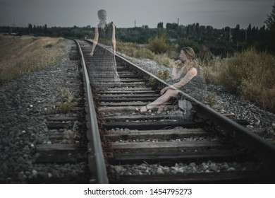 Lonely sad girl sitting on the rails of the railway and goes into the distance.Toned photo. Double exposure. Concept: depression, problem, unhappy love, separation, personality psychology.