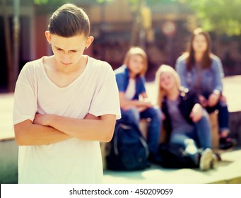 Lonely sad male teenager standing away from friends feeling depressed