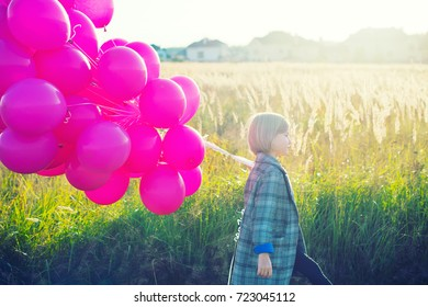 Lonely sad school girl walking in autumn field with colorful balloons at her birthday