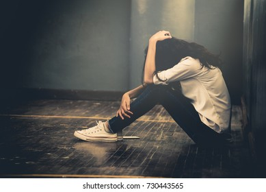 Lonely sad teenager student cry and hug her knees sitting in the dark corner ,Sad woman Unhappy and stressed student on the campus ,Family problems and education concept