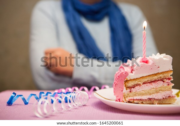 Lonely sad woman and birthday cake with burning candle