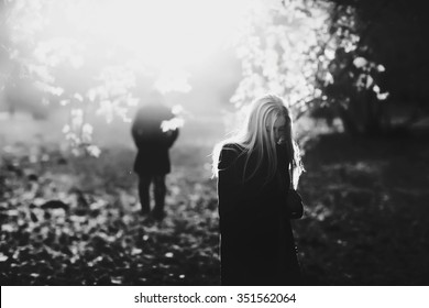 Lonely sad woman with blond hair wandering around the park, in the background silhouette of a man