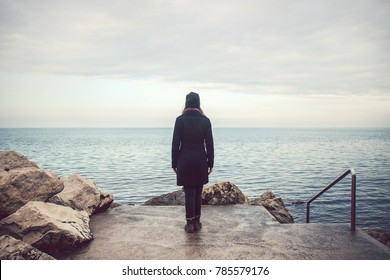 lonely sad woman looking the horizon, solitude concept in sea landscape with gray cloud (winter season)