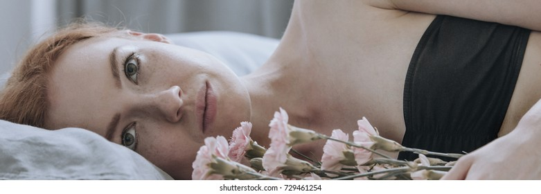 Lonely sad woman lying on the bed and holding flowers, longing for lost love