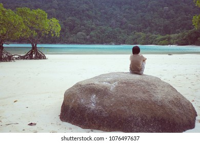 Lonely sad woman sitting on the big rock by the sea, vintage light.