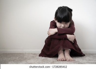 Lonely sad young girl is sitting in the corner wall and holding her knees, concept of domestic violence, abuse and harassment
