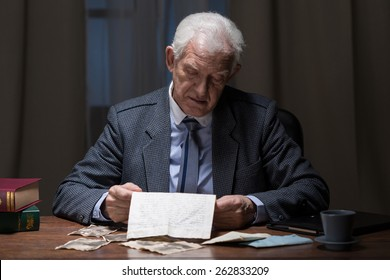 Lonely senior businessman spending night at the office