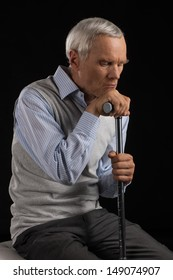 Lonely senior man. Disappointed senior man leaning at his cane while sitting isolated on black
