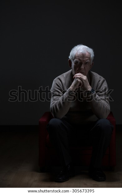 Lonely senior man sitting in a armchair