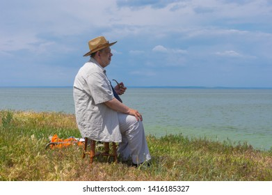 Lonely senior man sitting on a stool on abrupt riverside of the Dnipro river, Ukraine