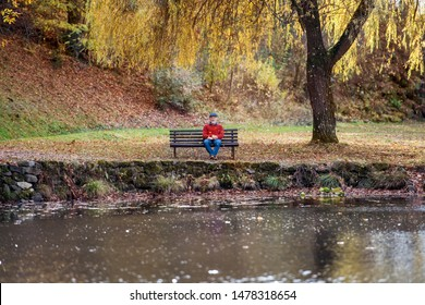 Lonely senior man sitting on bench by lake in nature, looking at camera.