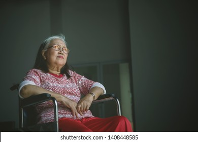 Lonely senior woman looks pensive while sitting in a wheelchair