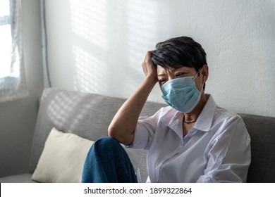 A lonely senior woman wearing a sanitary mark with a hand on her head has been a lockdown at home due to coronavirus, or COVID-19 diseases. And Aged woman in depression sadness.