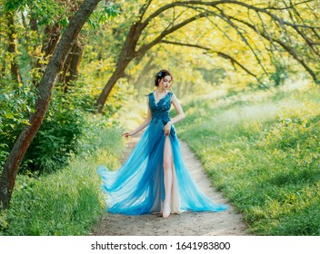 lonely sexy girl naked leg walk foliage green forest evening chic dress. hair decorated blue flowers of cornflowers. Elegant brunette hairstyle. sunny bright day nature summer spring wedding party art