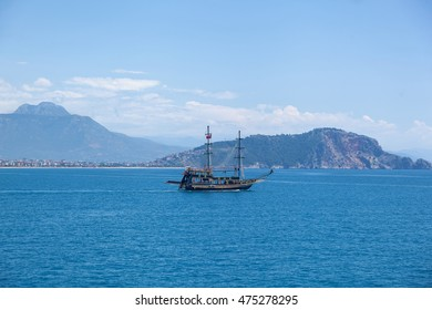 A lonely ship sails against the background of the mountains silhouettes, Lonely ship