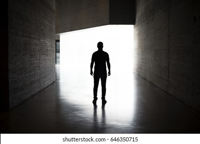 Lonely silhouette in dark architecture with light background. Full-length portrait of man on his back.