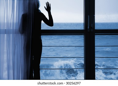 Lonely silhouette in a window on a background of the storm sea