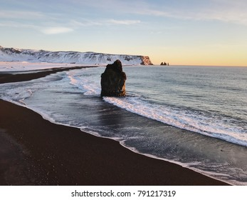 Lonely stone in the ocean at the black beach, Vlk, Iceland