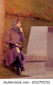 Lonely stylish woman  in coat sitting and thinking outdoors