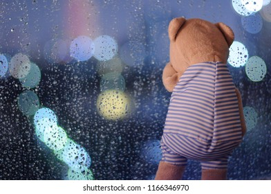 A lonely Teddy Bear crying at window with rain drop on the glass in rainy day isolated on bokeh light at night with space for text.