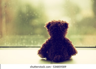 Lonely Teddy bear looking out the window on rainy day, vintage film grain added, retro style, selective focus