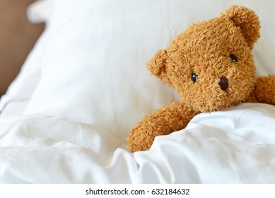 Lonely Teddy Bear lying on the bed. Concept about waiting for someone and loneliness. (Selective Focus on bear's eye)