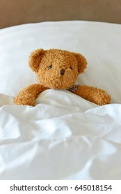 Lonely Teddy Bear lying on the bed. Concept about waiting for someone and loneliness. (Focus on bear's eye)
