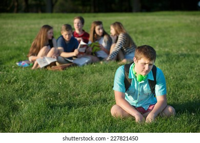 Lonely teen male sitting away from group