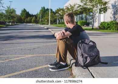 Lonely teenage boy sitting on curb next to high school.