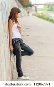 Lonely teenage girl leaning against concrete wall in urban environment.