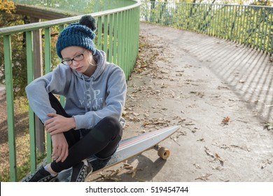 Lonely Teenage girl sitting on her skateboard on an urban footpath ramp, copy space on the right