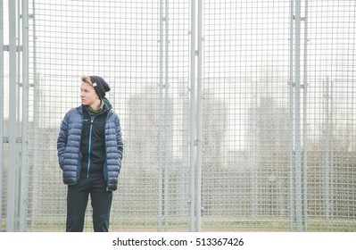Lonely teenager in city sport place  look throw metallic wall.