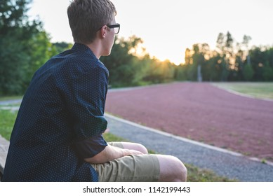 Lonely teenager sitting on a bench and looking at track/soccer field at sunset.