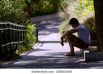 Lonely teenager sitting on the street