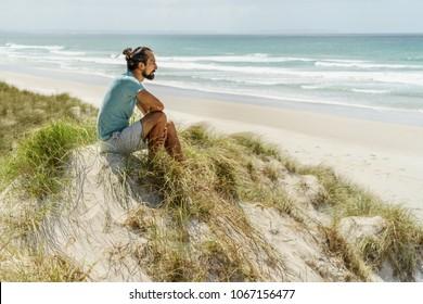lonely thoughtful man sitting on seashore and looking at sea, Rarawa beach, New Zealand
