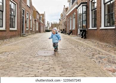 Lonely toddler girl in old village - Hindeloopen, Friesland, Netherlands