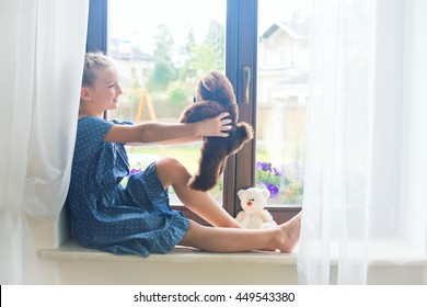 Lonely toddler russian girl sitting on sill near window at home playing teddy bears happy and funny. Colorful back yard at background