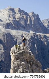 Lonely at the top. Climber standing alone on a pinnacle, rock peak. Crispein (Crispina), in the Puez-Geisl group, with Sella mountain in the background. Dolomites, Alto Adige, Italy.