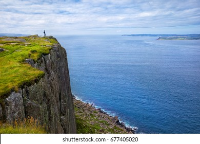 Lonely tourist with backpack standing on the cliff Fair Head and looking at Rathlin island, County Antrim, Northern Ireland, UK